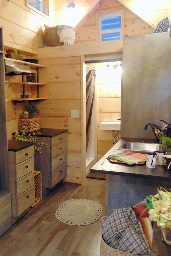 Incredible Tiny Homes gave the client's father use of their shop so he could build the kitchen cabinets for his daughter. He also built a fold down table that has an extension for when she has guests.