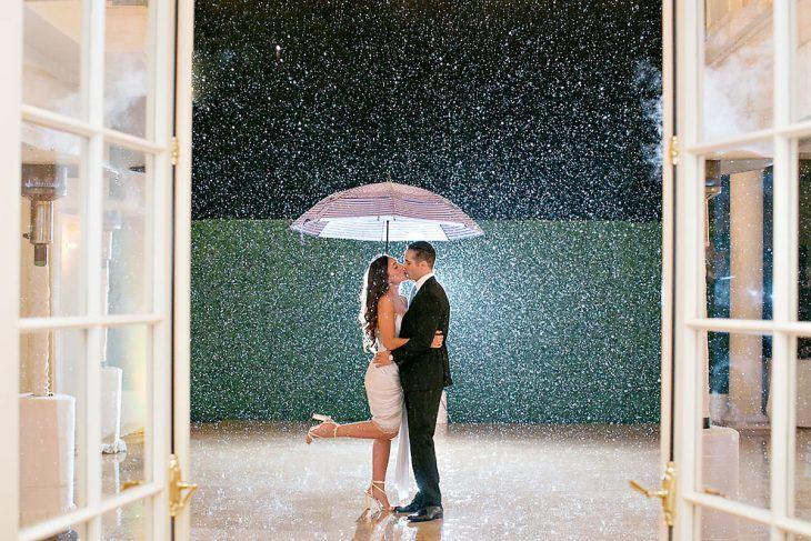 pareja andose un beso con paraguas bajo la lluvia
