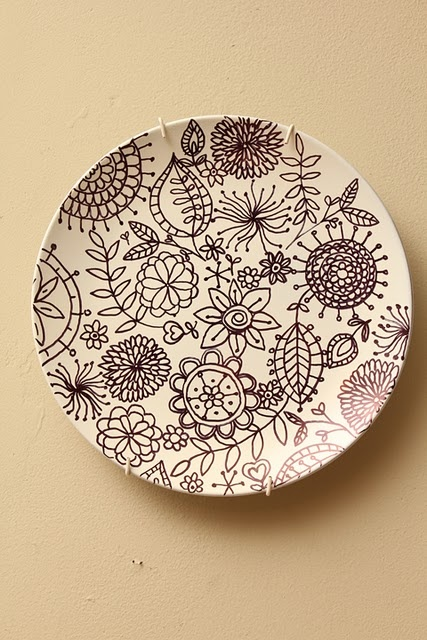 DIY Plate spray painted white & the design is drawn with a black Sharpie 2 or 3 plates on each side of the tv on the mantel