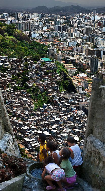 """photos from claudia jaguaribe's """"between hills"""" (2012) of rio de janeiro, as seen from the (no doubt intentionally claustrophoic) perspective of children in the favelas who can see the more affluent apartment complexes in the background"""