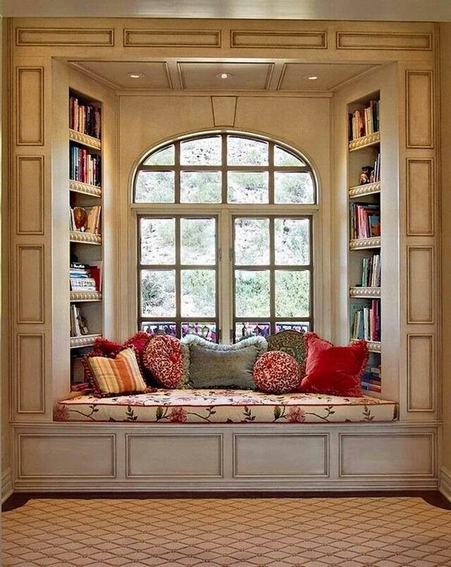 sitting bench under arched french windows with flanking bookshelves
