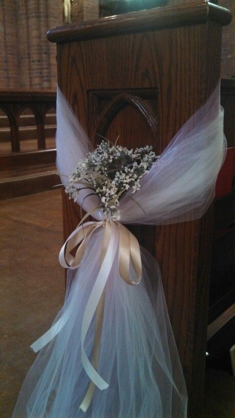 church pew decorations... this was so easy to do with some long pink and beige tule..and  the same colors of ribbon. Cut the Tulle to just grace the floor and then put some fake babies breath in there..easy!