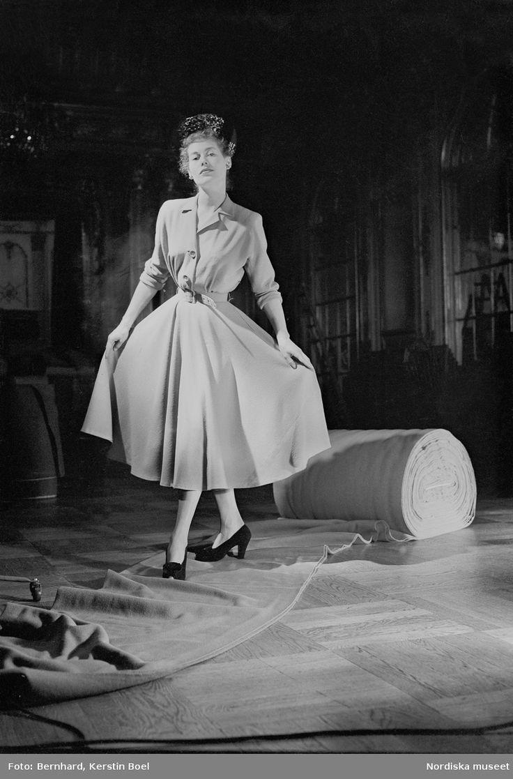 Mode för Ullkommittén, mannekänguppvisning på Grand Hotel i Stockholm våren 1948. Kvinnlig modell i ljus klänning går på utrullat tyg. Foto: Kerstin Boel Bernhard
