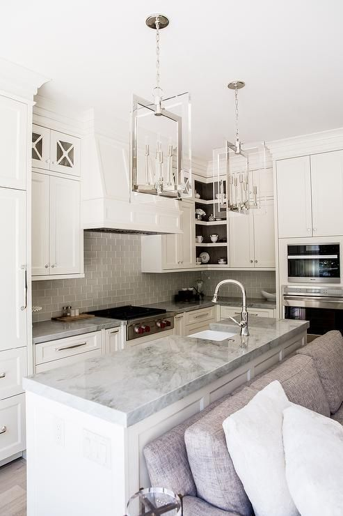 Stunning kitchen features creamy white shaker cabinets paired with Super White Quartzite countertops and a gray glass subway tile backsplash.