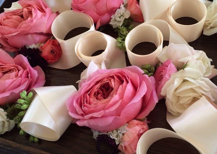 Lovely ribbon wrist corsages of pink romantic antique garden roses, white spray roses, pink ranunculus and larkspur buds.