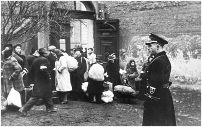 A Polish policeman supervises a deportation action in the Krakow ghetto