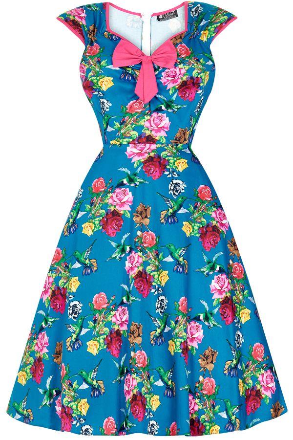 Lady V London Isabella Birds of Paradise  Šaty ve stylu 50. let. Nádherné šaty ve stylu retro z londýnské módní dílny, které vás uchvátí svým provedením. Nádherné šaty s výrazným vzorem barevných růží a kolibříků na modrém podkladě z vás udělají dámu ať už na společenské události jako je svatba, zahradní párty či při běžném nošení. Lemy kolem rukávků a krásně řešeného výstřihu v růžové barvě, kouzelná mašle jako třešnička na dortu (lze oddělat a připevnit na jiné místo na šatech nebo do…