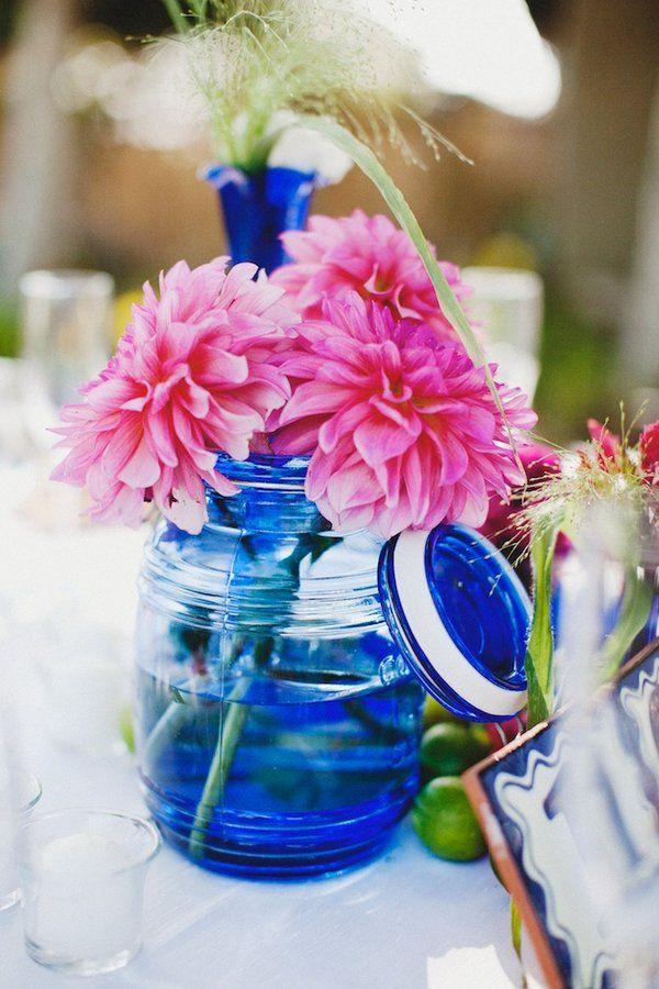 Un bocal coloré et quelques fleurs d'une couleur franche.