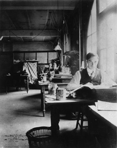 Tom Thomson as a graphic artist at Grip Limited, with JEH MacDonald seen in background at end of row, 1911 | Ontario Archives, via Vintage Toronto, FB