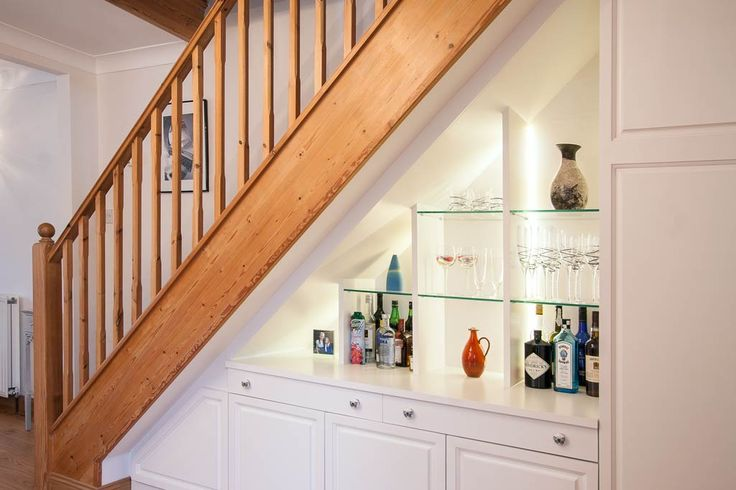 An excellent way to use that awkward understairs space - there's even a place for the ironing board and vacuum cleaner as well as the gin!