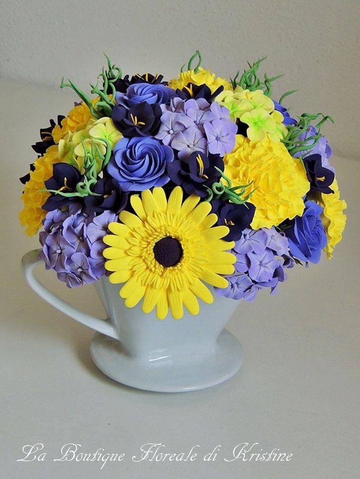http://mercatinoartigiano.net/it/annuncio/view?id=259 Una tazzina di fiori artigiano - Kristine Suibra Una tazzina di fiori che renderà la vostra casa ancora più allegra e colorata. L'abbinamento dei colori tra il giallo e il viola è perfetto. La composizione e composta dai garofani, le rose vittoriane, le gerbere, le fresie e le ortensie. I fiori e il verde sono fatti interamente a mano di argilla polimerica. L'altezza è di circa 20 cm (compreso la tazzina). Può essere realizzata in diversi…