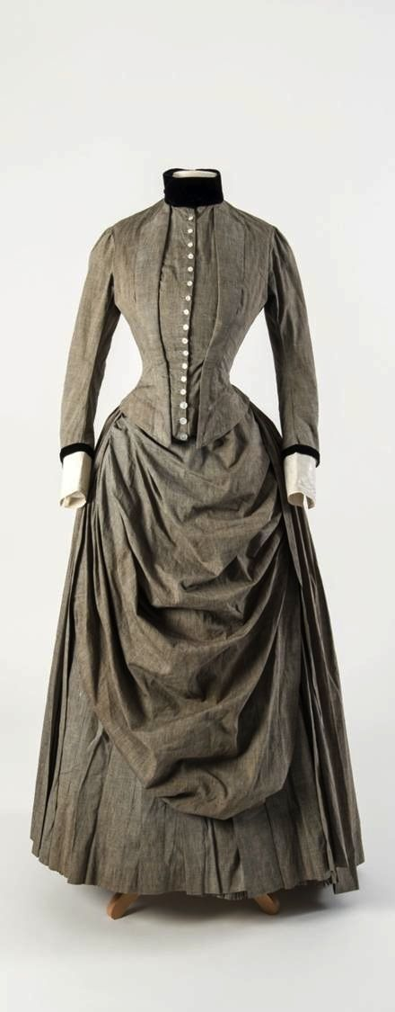 Grey cotton dress with draped apron front and black velvet trimming at collar and cuffs, late 1880s, at the Fashion Museum Bath. Photo courtesy of @Fashion_Museum on Twitter.