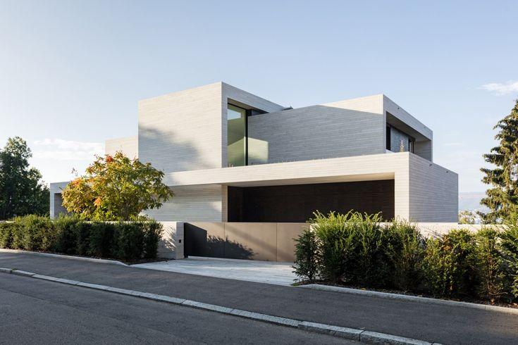 neubau villa zürich strassenfassade dietfurter kalkstein zufahrt tor tageslicht