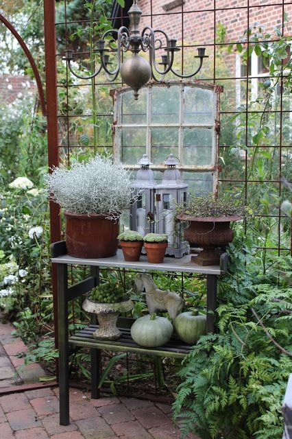 <3 this Autumn vignette - lanterns with an old window, green gourd/pumpkins, planters and chandelier