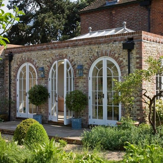 Opt for an orangery Orangeries have a more substantial look than conservatories, with brick walls and tall, elegant windows. This beautifully proportioned one has five sets of arched double doors and a large lantern roof to flood the space with light.