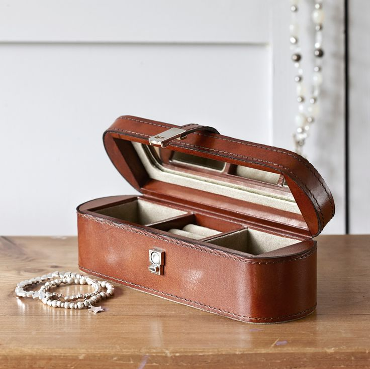 Our small leather jewellery box makes a wonderful and useful gift as it is perfect for storing essential jewellery pieces. Neat and compact with rounded edges it is ideal for packing in your luggage or just placing on a bedside table as a storage box for everyday jewellery.  Inside are two compartments suitable for a ladies watch or necklace and a central padded section for rings and earrings together with a small mirror. A magnetic clasp closes the box securely.  We are happy to offer you…