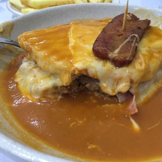 Steffani Cameron's hunt for the perfect Francesinha sandwich in Porto, Portugal - via Vancouver Courier 02.03.2016 | What, then, is a Francesinha? Imagine a sandwich layered with a filet of steak, some ham and spicy linguiça sausage covered with a generous helping of cheese, baked until melty and puddling around the bottom. Then, because that's not enough, smothered in a spicy beer-tomato sauce.