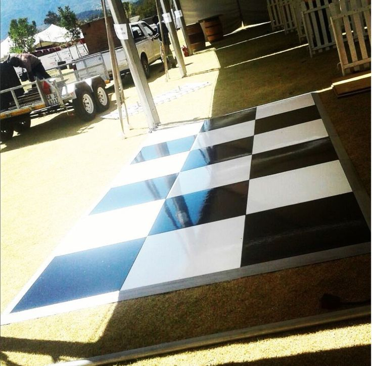 a black and white check painted floor at a festival - making the stand pop. #connectafloorcape #eventflooringcapetown