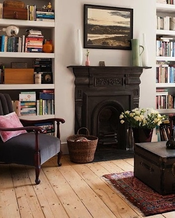 Fireplace, woven basket, rug, low wooden table, in-built shelves, wall colour - love