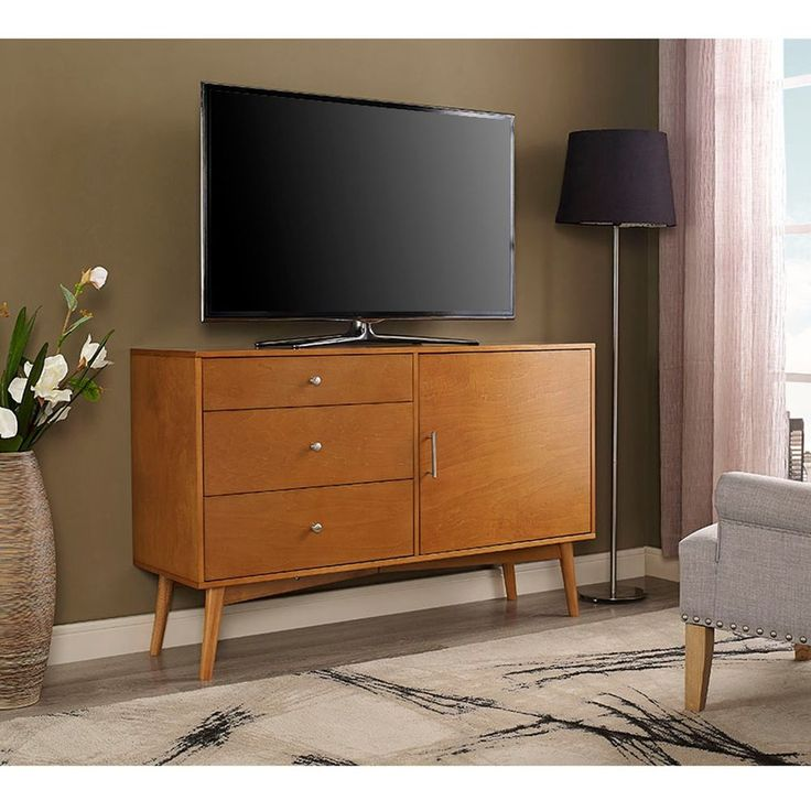 """Your living or entertainment room can look even more stylish with this angelo:HOME Mid-Century TV Stand. Crafted from durable mdf, this flat panel TV stand is designed for TVs up to 52"""" wide. The versatile design features three large drawers, side cabinet with adjustable shelving, and a cable management function at the back. 
