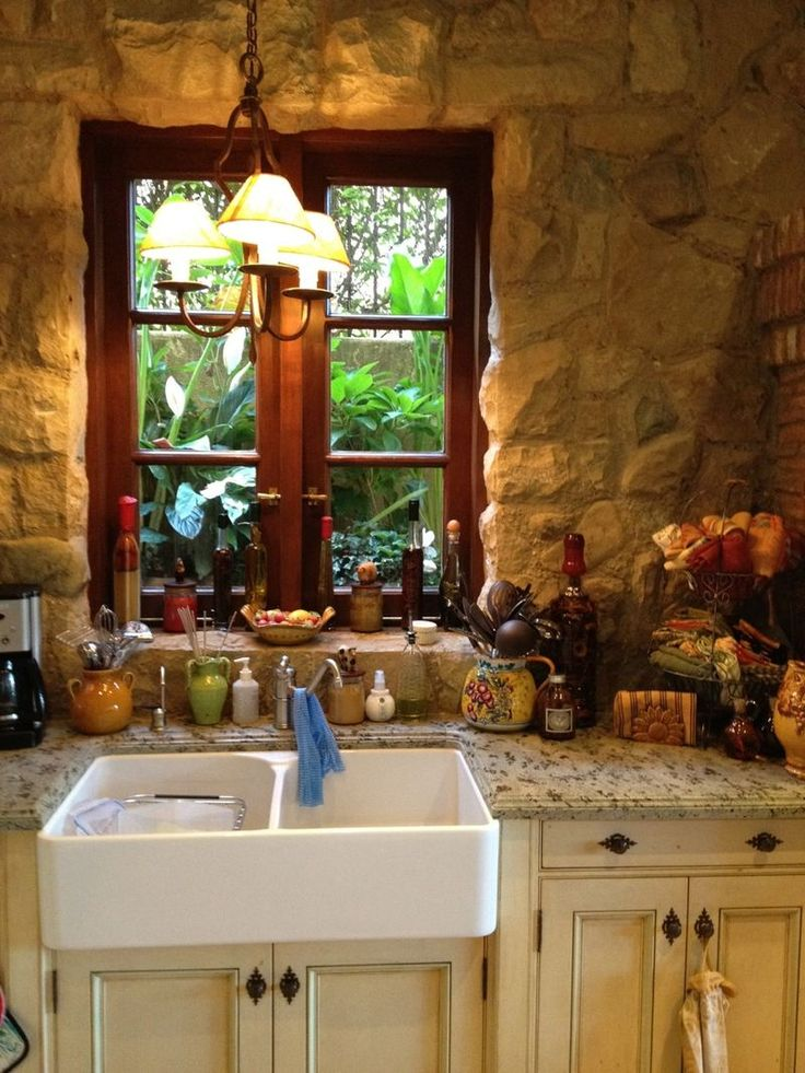 The stone wall, wood window and farmhouse sink with granite counter all give it an old world, French country feel.  I love that style.  I would have placed the light in the middle of the window.  It is not centered and that would drive me crazy. Just sayin!