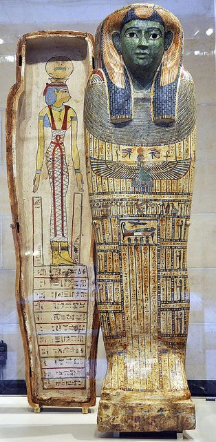 "Coffin of Ta-mit. The front of the coffin is painted with pictures and magical prayers in hieroglyphs. They were intended to guide and protect a woman named Ta-mit after her death as she faced her last judgment. Her mummy disappeared long ago, but her name (which means ""she-cat"", or Cat Lady) is preserved on the coffin lid (look for a cat hieroglyph near the top of the fifth column beneath the scene of Ta-mit's mummy lying on a bier). The sky goddess Nut (NOOT) spreads her wings…"
