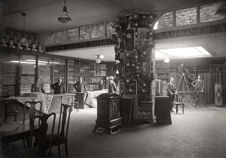 Interieur van stoffenwinkel magazijn de zon aan de Ferdinand Bolstraat in Amsterdam, met een aantal verkopers achter de toonbank en in de winkel. Nederland, 1916.