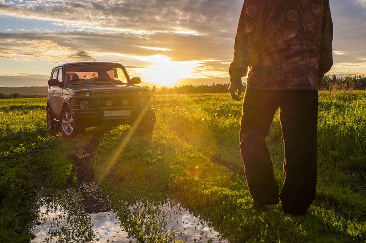 Mari man walking toward car at sunset in rural field - Mari man walking toward…