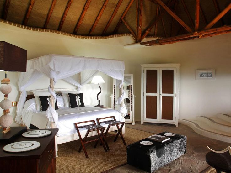 Located on a Masai game reserve in Southwestern Kenya, this luxurious suite employs traditional African construction techniques like lofty rough-hewn wood-beamed ceilings, mud walls and a woven grass roof. A gauzy canopy bed, an animal hide bench and tribal textiles exemplify African elegance. Image courtesy of Olarro Lodge