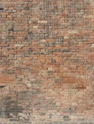 Old red brick wall with rough surface and dark spots and streaks.