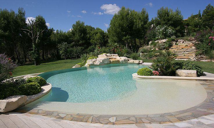 Diese Anlage erinnert an eine Lagune, die die Sehnsucht nach Sonne, Strand und Meer im eigenen Garten befriedigt. Obwohl künstlich angelegt wirkt der Pool mit seinen fließenden Formen und seinem großzügigem Einstiegsbereich natürlich und gleichzeitig stilvoll.