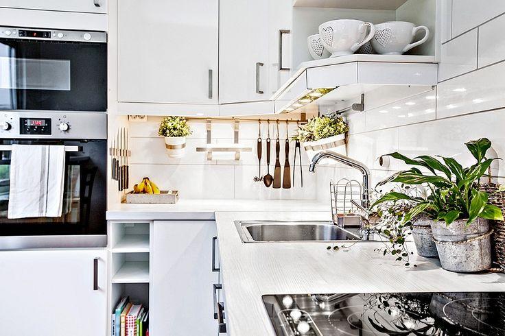 Stilrent välutrustat kök med vita högblanka luckor som renoverades 2011