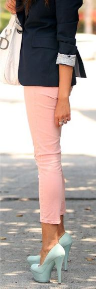 Pastel pink ankle jeans paired with blue pastel pumps and a simple black blazer and white purse.