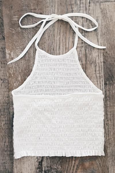 Our best selling quality halter top is back! Whitecolored halter top features self-tie neck and open back. Top is semi cropped (below the belly button) and has