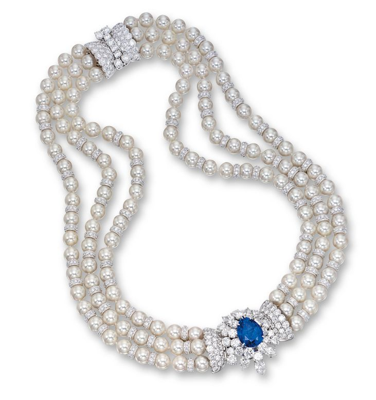 Sapphire, cultured pearl and diamond necklace by Harry Winston. Centring on a pear-shaped sapphire weighing 10.15 carats, surrounded by a cluster of brilliant-cut and pear-shaped diamonds, to a triple strand necklace composed of cultured pearls measuring approximately 7.00 to 7.50mm, decorated at intervals by brilliant-cut diamond-set rondelles, completed by a stylised clasp set with brilliant-cut diamonds, the diamonds together weighing approximately 26.80 carats, mounted in platinum…
