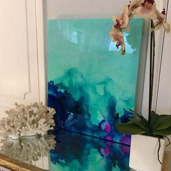 Un d'une œuvre d'art abstrait genre est un mélange de couleurs acryliques et encres avec un revêtement de résine pour créer un résumé vraiment unique et serein original. La peinture a une verre «couche» de résine époxy afin d'ajouter un éclat brillant épais à la pièce. Est très beau dans la lumière naturelle!  Les couleurs comprennent les nuances de l'or, blanc, bleu, gree, aqua, lilas, irisée de paillettes et des touches de véritables feuilles d'or.  Il s'agit de toile robuste originale…