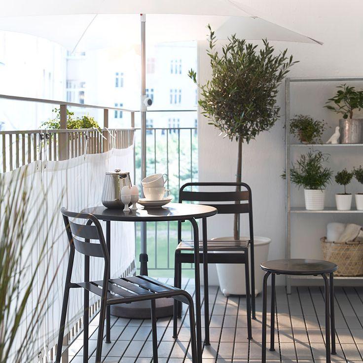 Balkon z białym parasolem, szarym okrągłym stołem, stołkiem i krzesłami oraz białą osłoną przed wiatrem/słońcem