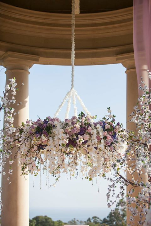 This pastel pink and purple floral chandelier is perfect for a lavish wedding - you can scale it back for a smaller ceremony ~ https://www.insideweddings.com/weddings/pastel-pink-purple-celebration-at-the-resort-at-pelican-hill/591/