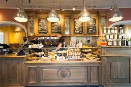 The Caffè Nero scheduled to open soon in Boston will resemble its other shops, such as one in Poland (left) and one in Cyprus (right).