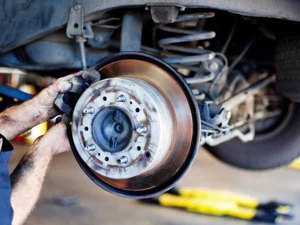 mechanik naprawiający układ jezdny samochodu