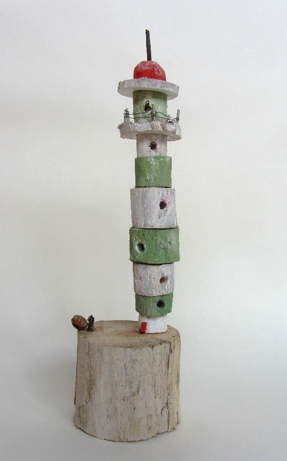 Green and white lighthouse made from driftwood.