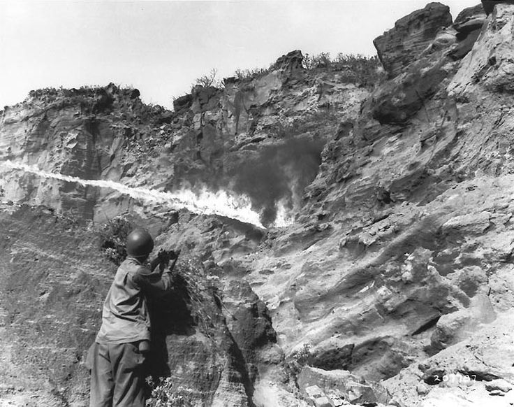 Flame thrower in use against Japanese holding out in a cave along Iwo Jima's northern coastal cliffs, 8 April 1945