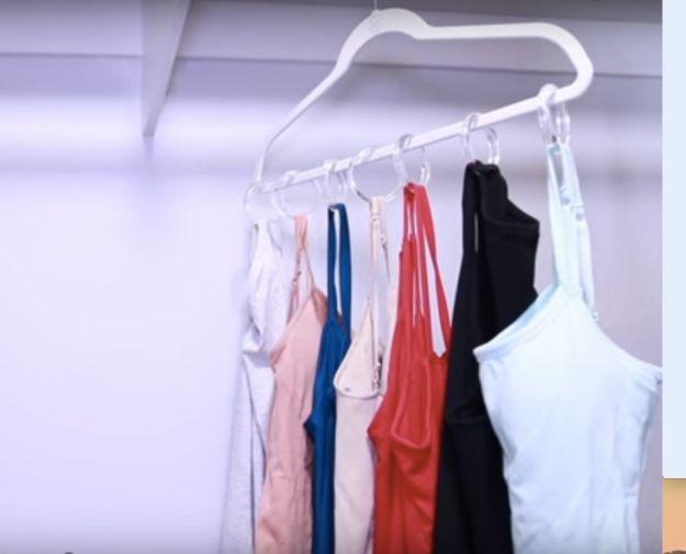 Em vez de pendurar todas as suas blusas de alcinha em vários cabides, prenda aros de cortina de chuveiro em um cabide e deixe todas elas em um só lugar.