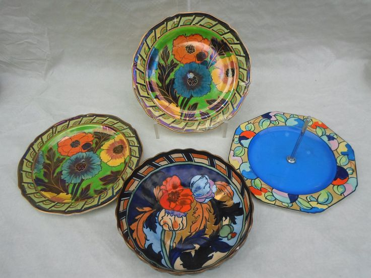 A 1920s Wood & Sons Bursley Ware bowl, designed by Charlotte Rhead in the 1550 pattern, having a tube-lined decoration of poppies enamelled in various colours on a blue ground with gilt finish, together with two lustred cake stand plates in the 1992 pattern (lacking stand fitting) and a cake stand base in the 577 pattern, each also designed by Charlotte Rhead