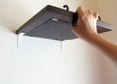 Here is a simple way to hang artwork or shelves in your suite without using nails and harming your walls.