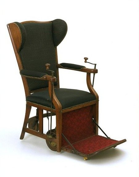 "Example of Viola's Merlin Chair [A ""Gouty Chair"" This chair is designed as a comfortable wing arm-chair on wheels. Winding handles on the arms propel the chair along. Invalid chairs had been used since the 17th century but chairs of this type were popularised by the inventor John Joseph Merlin, who designed a more up-to-date version. We do not know who made this example, but similar chairs were made by the cabinet-making firm Gillow & Co"