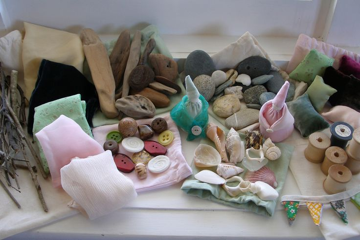 Small collections and their storage bags - sticks, tiny cushions, buttons and beads, shells, driftwood, stones, wooden cotton reels - plus textured fabric and tiny dolls.