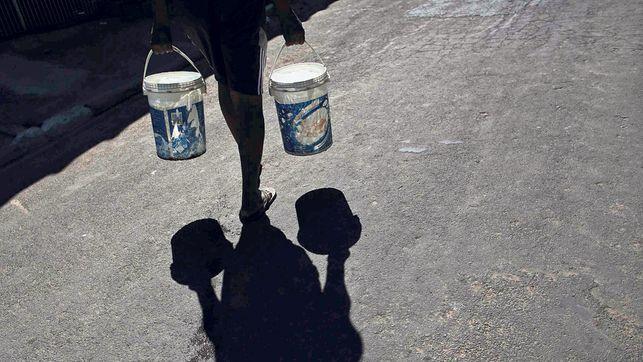 Zu den beunruhigenden Problemen gehört die Wasserknappheit: Ein Mann holt Wasser von einem Tanklastwagen.