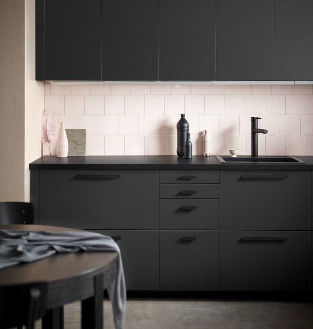 Kjøkken med matte antrasittgrå fronter av 100 prosent resirkulert avfall kombinert med svarte håndtak, oppvaskkum og blandebatteri. Veggen er dekket med rosa fliser.