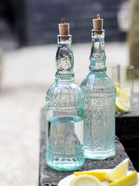 Toscaanse fles - Happinez Of je er nu water, limonade of olie in doet, in deze rijk gedecoreerde flessen komt alles tot z'n recht. Het ontwerp wordt al ruim een eeuw ambachtelijk geproduceerd in Italië. De mooie zachtgroene kleur danken de flessen aan een percentage gerecycled glas. Zowel in vierkante als ronde vorm verkrijgbaar, compleet met kurk met koperen greepje.